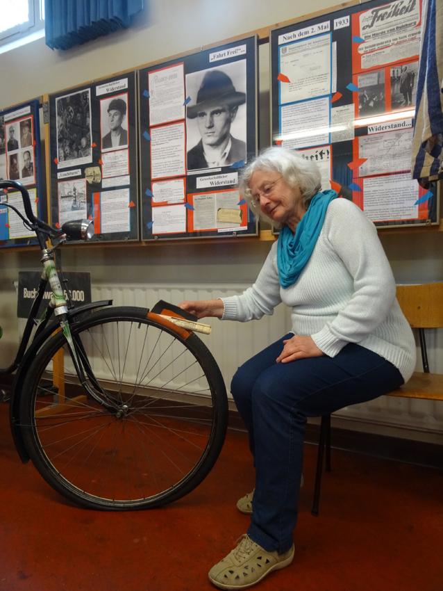 Christa Bröcher demonstriert, wie Flugblätter in einem Fahrrad versteckt transportiert wurden. Foto: Petra Grünendahl.