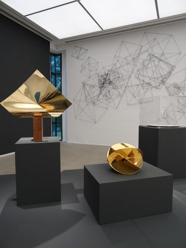 """On Surface - An der Oberfläche: Max Bills Skulpturen aus vergoldetem Messing (vorne), Heike Webers """"cubes"""" (2016, hinten). Foto: Petra Grünendahl.,"""